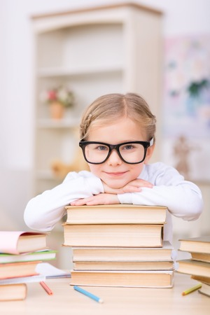 womanhood: Schoolgirl and books. Little charming girl is smiling while leaning on a pile of her books at the desk.