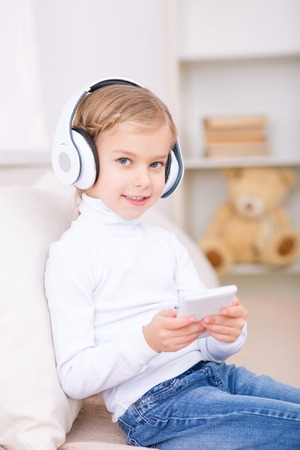 womanhood: Enjoying the music. Little girl is sitting on the sofa and listening to music by using headphones and smartphone. Stock Photo