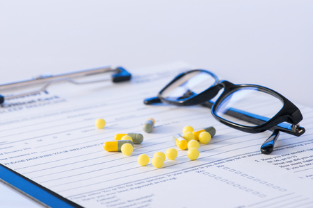 questionary: Hospital vibe. Bunch of yellow vitamin pills along with eyeglasses are resting on top of hospital documental form.  Stock Photo