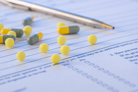 pacientes: Pluma y medicinas. pastillas de color amarillo y la pluma están en la parte superior del formulario de pacientes historia.
