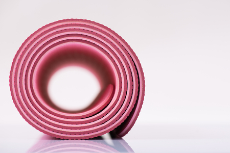 vigorously: Ready for exercises. Rolled up pink yoga mat is on reflecting surface.