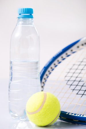 water surface: Ready for sports. Tennis racquet along with ball and bottle of water on the surface.