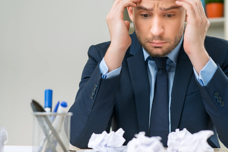 cheerless: Find the way out. Cheerless gloomy meditating office worker holding his head and feeling distempered while sitting at the table Stock Photo