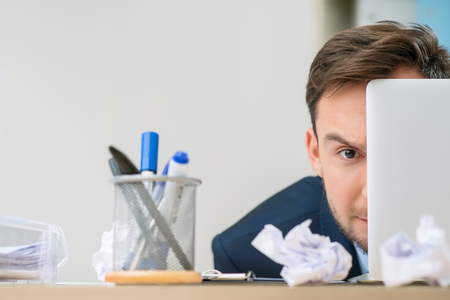 penetrating: Penetrating glance. Close up of pleasant handsome serious office worker sitting at the table while looking out of the laptop