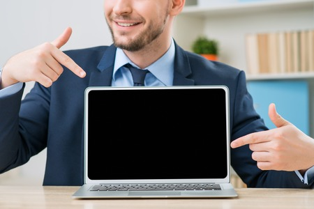 feeling up: My right hand. Close up of positive smiling office worker sitting at the table and pointing out his laptop while feeling overjoyed Stock Photo