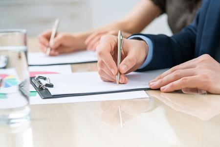 diligente: Involucrados en el trabajo. enfoque selectivo de empleado de oficina diligente sentado en la mesa y haciendo notas con su colega de trabajo en segundo plano Foto de archivo