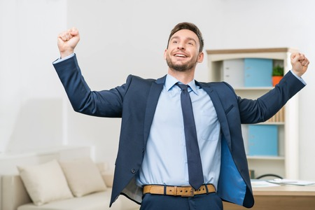 elated: Feeling on the edge of glory. Full length of  overjoyed elated office worker holding his hands up and feeling content