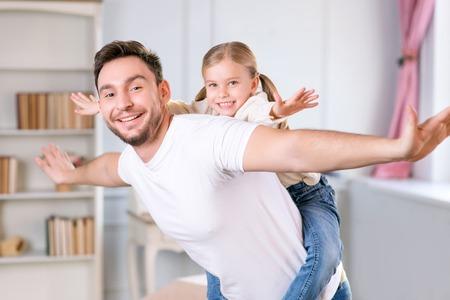 私は、私が飛ぶことができると考えています。背面に彼女の娘を保持再生に関わり合いながら手をわき保つこと喜んでの快活な父のクローズ アップ
