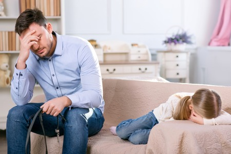 cheerless: Unpleasant moment. Cheerless moody father holding belt and going to punish his daughter who is crying while lying on the sofa Stock Photo