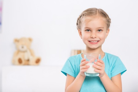one room school house: Drinking milk. Smiling schoolgirl is standing and holding her glass of milk.