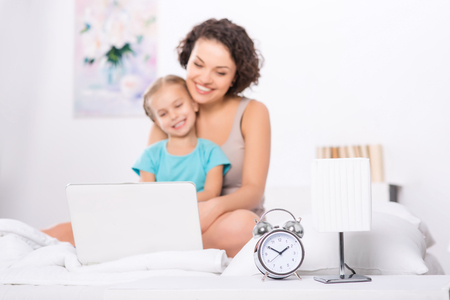 parentage: Daytime activities. Selective focus on the clock while mom and daughter are busy with laptop. Stock Photo