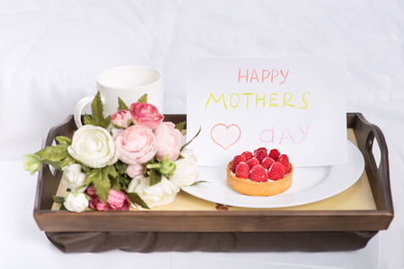 cup cakes: Perfect greeting. Festive breakfast containing fruit cake with coffee, flowers and card is on a wooden tray.