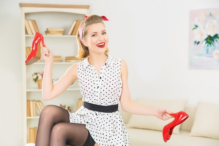 appealing: Playing with shoes. Young appealing smiling woman is upholding her shoes by the heels in playful way.