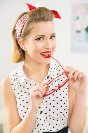 appealing: Posing with glasses. Young appealing woman is smiling while holding her glasses. Stock Photo