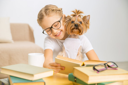 Leestijd. Little schoolmeisje zit op het bureau en het lezen met terriër op haar schoot.