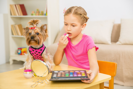 eyeshades: Getting ready. Little girl is applying lipstick while her pet dog sitting beside her on the table. Stock Photo
