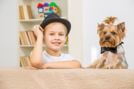 good times: Good times. Little smiling girl in black hat with her pet dog wearing elegant bowtie.