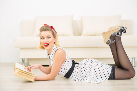 appealing: Liking the book. Young appealing woman is pointing at the book excitedly while lying on the floor.