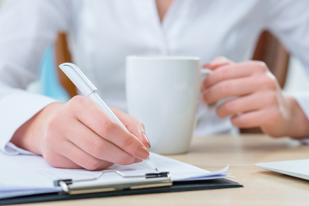 diligente: trabajador diligente. Agradable empleado de oficina femenina sentada en la mesa y tomar notas mientras bebe t� Foto de archivo