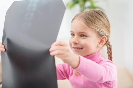 radiogram: Interesting thing. Positive curious little girl holding her radiogram and attentively examining it while expressing gladness