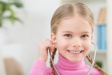 stethoscope: Want to be a doctor. Cheerful cute little girl holding stethoscope and playing with it while feeling happy Stock Photo