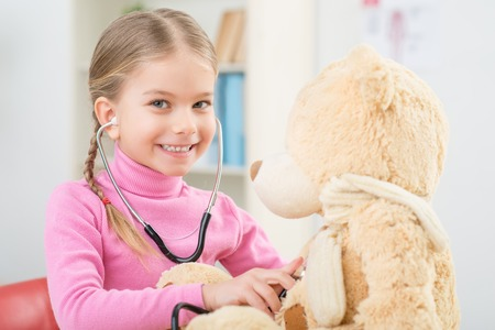 stethoscope: Like a real doctor. Positive pleasant smiling little girl holding stethoscope and examining her toy while feeling content Stock Photo