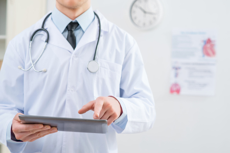 medical exam: Stay in touch with time. Close p of tablet in hands of professional pleasant doctor holding it while going to work