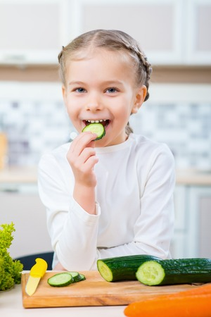 expressing joy: Happy childhood. Positive delighted cute little girl eating cucumber and expressing joy while sitting in the kitchen