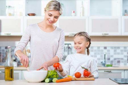 aceite de cocina: Alimentación saludable. madre positiva vivaz y su hija que hace la ensalada mientras se cocina en la cocina junto