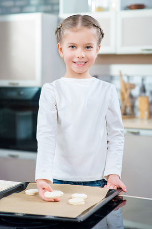 oven tray: Involved in process. Cheerful overjoyed nice little girl putting cookies on the oven tray while baking in the kitchen