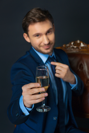 going for it: Toast for you. Close up of chalice of champagne in hands of confident cheerful businessman holding it while going to drink