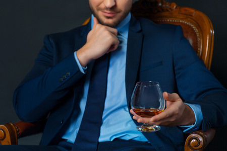 luxurious lifestyle: Luxurious lifestyle. Close up of relaxed handsome confident businessman sitting in  armchair and drinking cognac