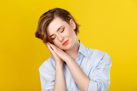 womanliness: Need some sleep. Young beautiful woman imitating tiredness and sleep with closed eyes and her hands next to face.