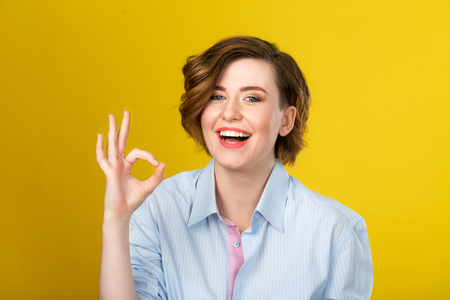 womanliness: Well done. Young stunning woman is smiling and giving a positive hand gesture isolated on the yellow background.