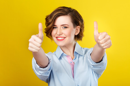 expressive mood: Everything is awesome. Shot of happy young woman cheerfully showing hand gesture and smiling.