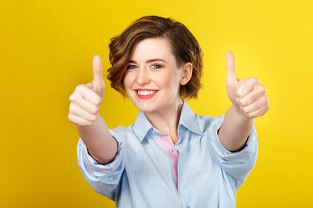 Tutto è impressionante. Colpo di giovane donna felice che mostra allegramente gesto della mano e sorridendo.