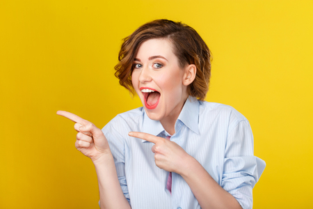 womanliness: Feeling excited. Gorgeous young woman is looking stunned and making pointing gesture with her hands. Stock Photo