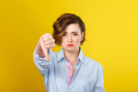 womanliness: Unpleasant twist of fate. Young nice woman looking upset and disappointed while making a gesture with her hand. Stock Photo