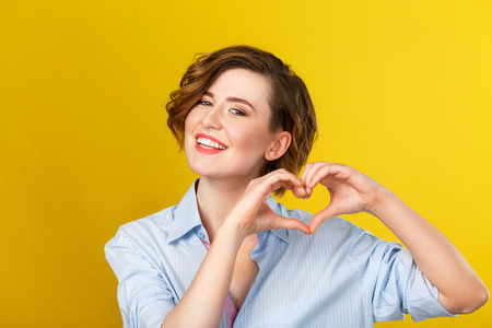 womanliness: Love is in the air. Attractive young woman is looking happy and showing a heart gesture with her hands. Stock Photo