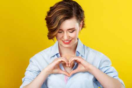 In my heart. Beautiful smiling woman is making a love gesture with her hands and looking happy.