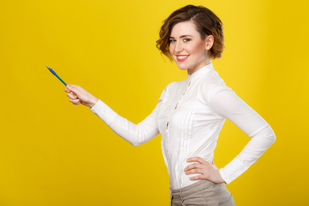 womanliness: School teacher. Pretty young lady is pointing towards copyspace with a pen and smiling attractively.