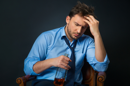 cheerless: Solve problems. Cheerless drunk man holding bottle with alcohol and drinking it while sitting in armchair isolated on black background Stock Photo