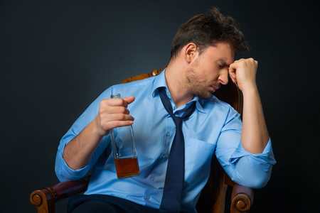 cheerless: Life is a hell. Moody cheerless man sitting in armchair and drinking alcohol Stock Photo