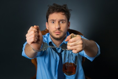cheerless: Slave of my habit. Cheerless poor man holding bottle with alcohol and  wearing handcuffs  while  begging for help
