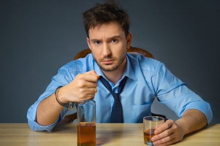 cheerless: In thrall. Cheerless drunk man holding bottle of alcohol in handcuffs and sitting at the table while drinking