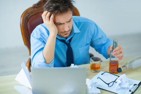 cope: How to cope with it. Cheerless man sitting at the table and working on the computer while drinking alcohol Stock Photo
