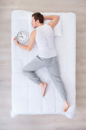 sleepy man: Wake up. Top view of sleepy man lying in bed and going to wake up in the morning Stock Photo