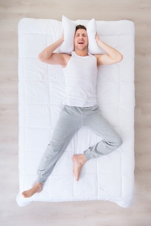 dreadful: Dreadful pictures. Top view of frightened man lying in bed and holding pillow while having nightmare