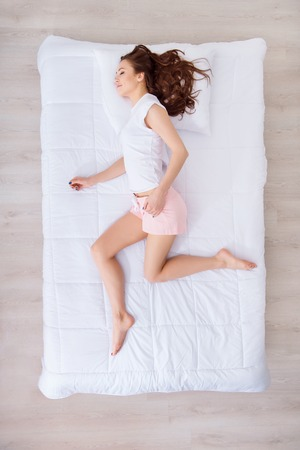 bedclothes: True runner. Pleasant woman lying in bed and imagining running while sleeping