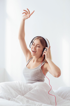 enjoyable: Enjoyable awakening. Young attractive woman is listening to music and moving with her hand up